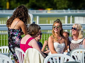 Group of ladies sitting at a table in the picnic area at Windsor Racecourse.