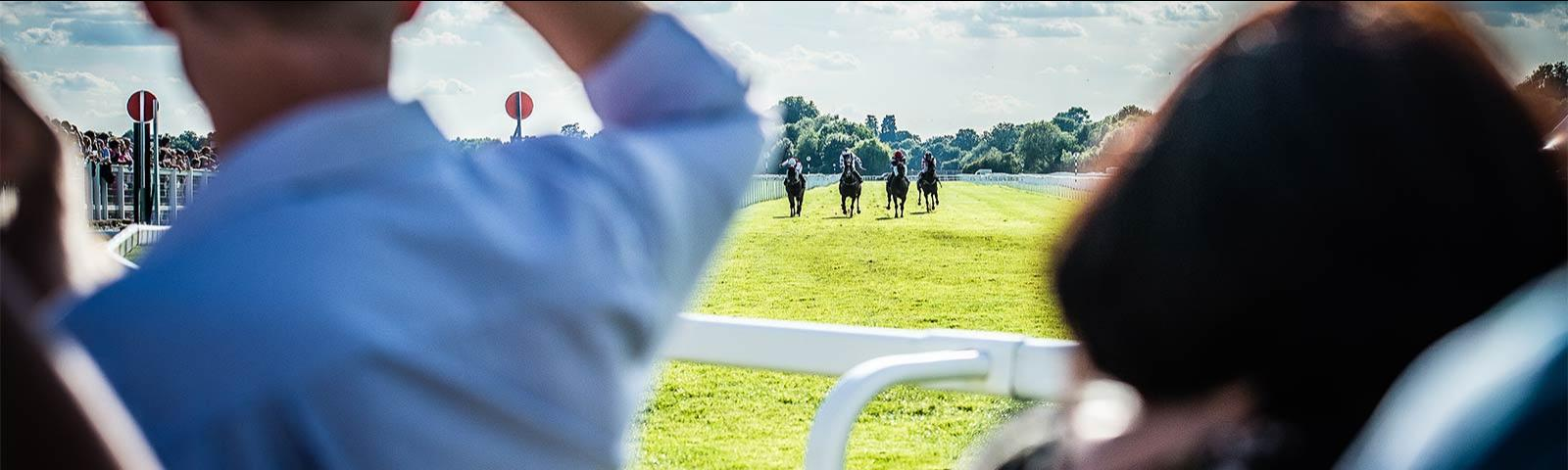 Jockeys racing at Windsor Racecourse with racegoers looking on.