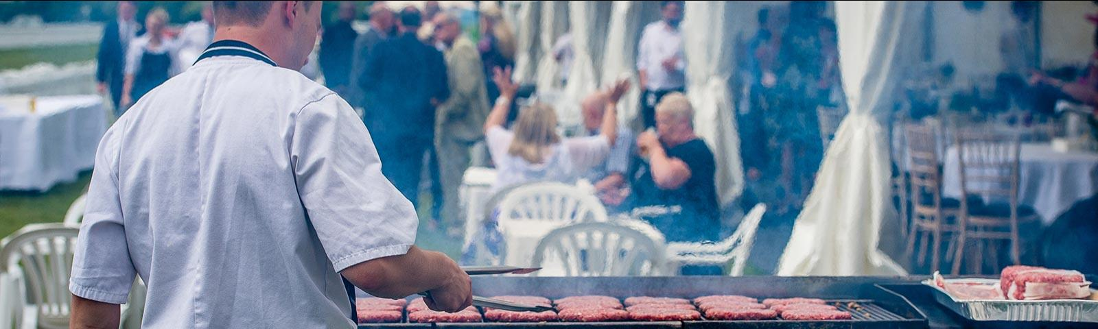 Chef preparing burgers on an outdoor grill at Windsor Racecourse.