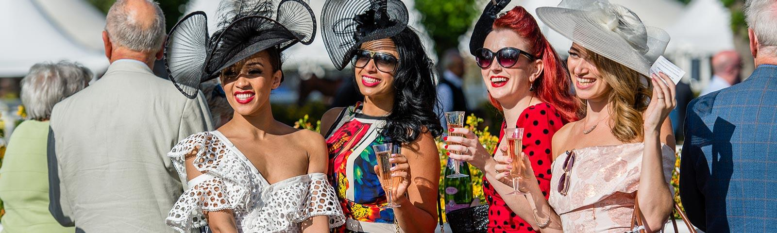 Four well dressed ladies drinking Champagne at Royal Windsor Racecourse ladies day