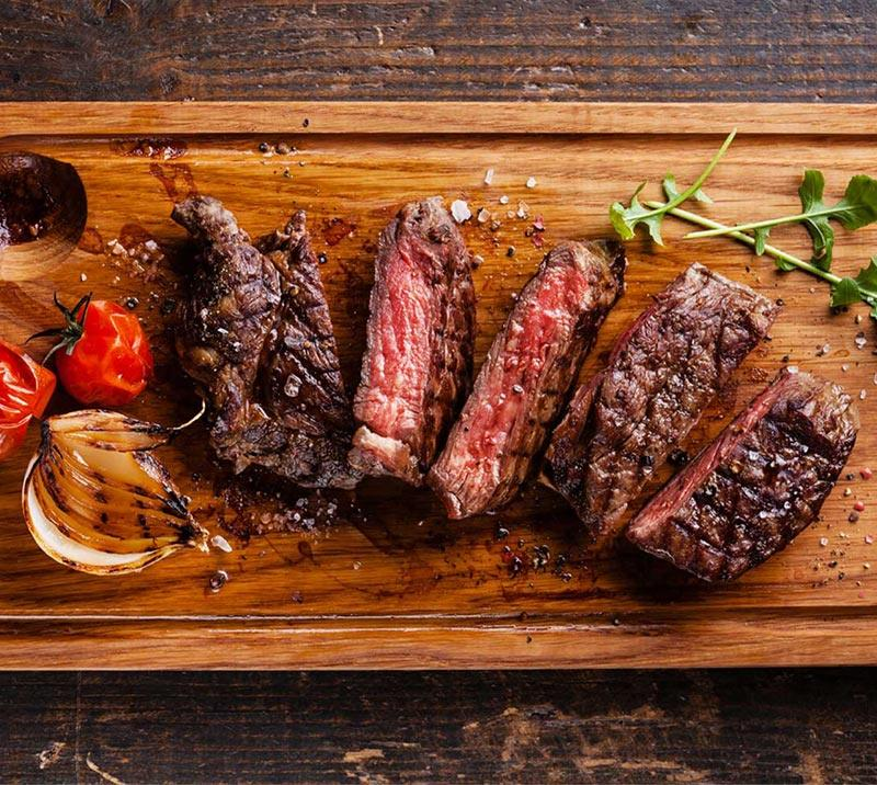 Close up on five pieces of grilled steak  laid out on a wooden plate.