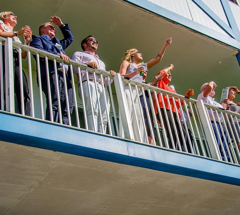 People enjoying a race at Royal Windsor Racecourse from  a balcony