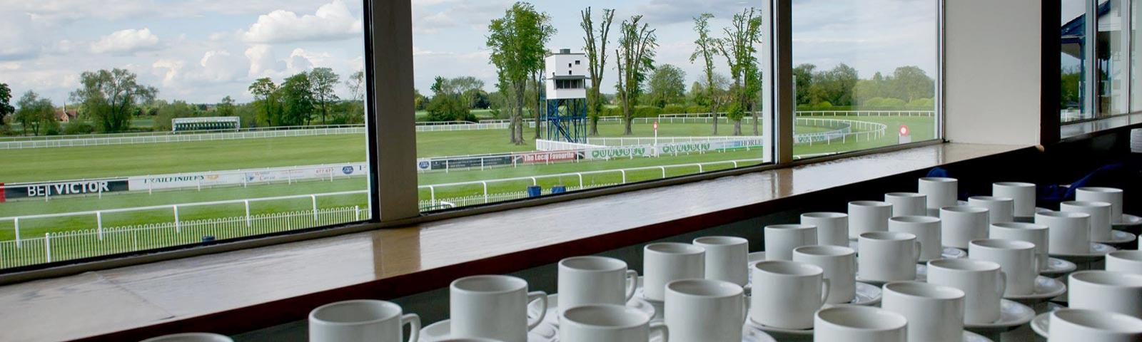 Fresh cups and saucers on a table with the green turf of the Royal Windsor Racecourse track visible outside.