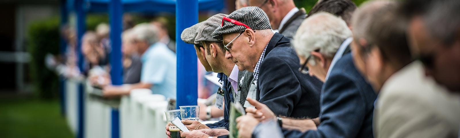 Gents in flat caps watching a racing during gentleman's day at Royal Windsor Racecourse