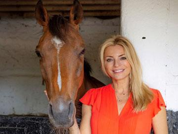 Tess Daly standing with a horse