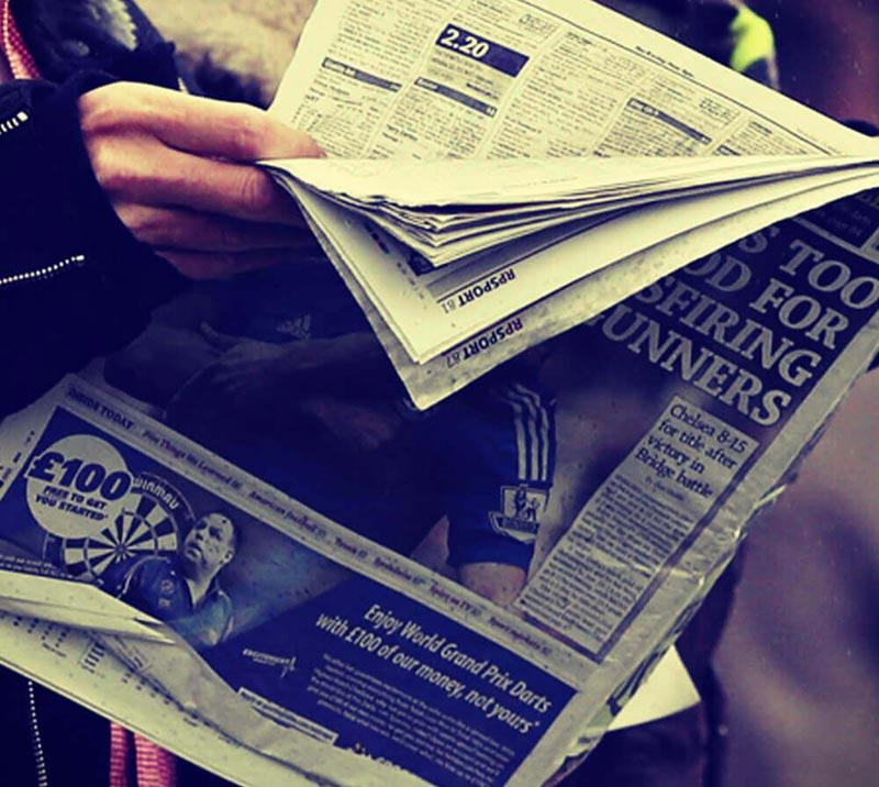 A race goer reading the racing post at Royal Windsor Racecourse