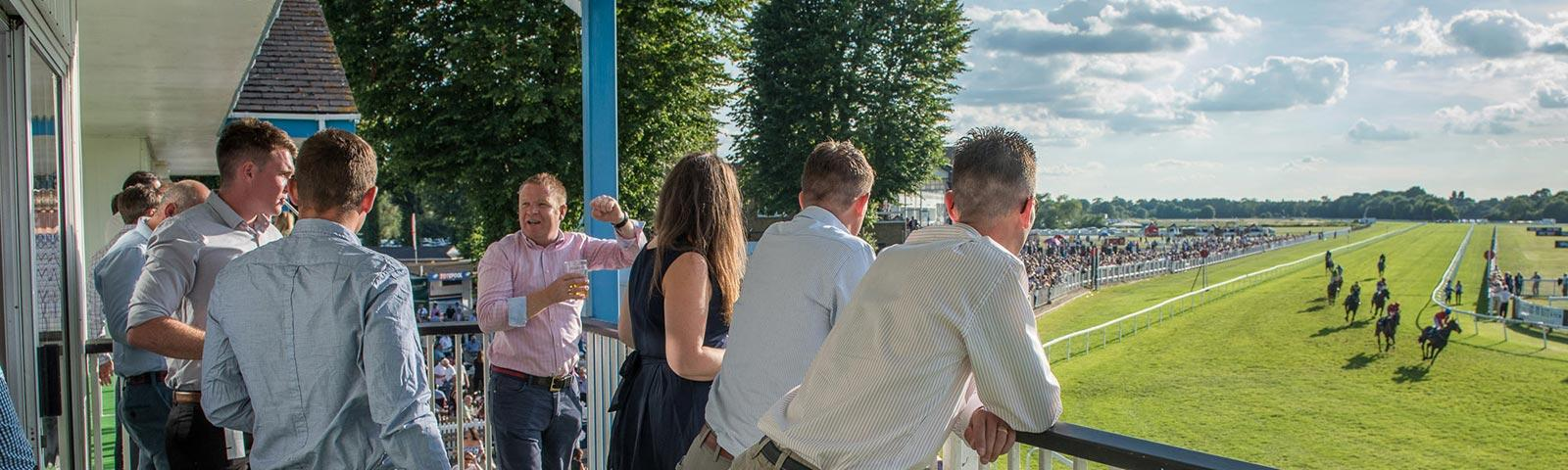 Friends get a great view of the racing action from the balcony within the Paddock Pavilion Boxes at Royal Windsor Racecourse.